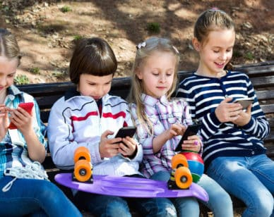 Group of cheerful children posing at urban street with mobile devices